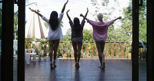 Three Girls Stretching On Terrace In Morning Back Rear View, Looking At Tropical Garden. Slow Motion 60 stock video