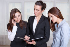 Three girls are studying the information in a folder Royalty Free Stock Photos