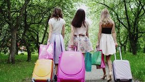 Three girls with suitcases, shopping paper bags in park on vacation, back view. Three young woman friends walk with suitcases in park, back view. Carrying stock video