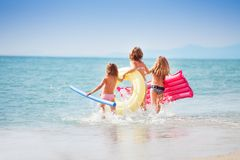 Three girls with swimming tools running to the sea Royalty Free Stock Image