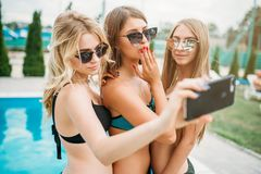 Three girls in swimsuits ad sunglasses make selfie Stock Photo