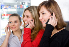 Three girls talking by mobile phones Stock Image