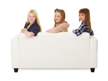 Three girls teens sitting on the couch Royalty Free Stock Photo
