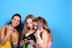 Three girls with telephone and camera Stock Photos