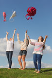 Three girls throw up bags and look up. At green grass at background of blue sky Stock Photo