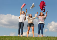 Three girls throw up bags and stand at grass. Three girls throw up bags and stand at green grass at background of blue sky royalty free stock photography