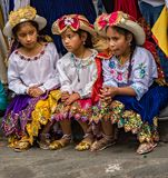 Three girls in traditional Ecuadorian clothes sit on street curb Royalty Free Stock Image