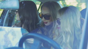 Three girls traveler driving a car in the car with a map stock footage
