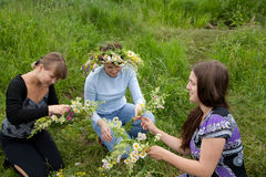 Three girls is twist flowers into a wreath Stock Photo