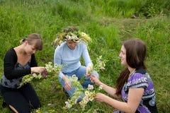 Three girls is twist flowers into a wreath. Three girls is twine a wreath of flowers at meadow stock photo