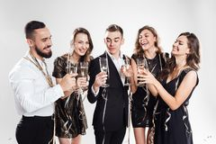 Three girls and two guys dressed in stylish elegant clothes stand together and clink glasses with champagne on the white royalty free stock photo