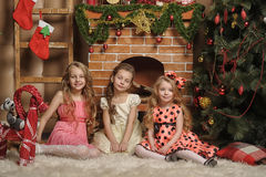 Three cute girls waiting for Christmas Stock Photography