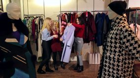 Three girls walk in a clothing store, they look at clothes and try it on. Three young fashionable women, a blonde and a brunette, choose clothes in a stock video footage