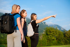 Three girls on a walk in nature. Three girls with backpacks on a walk in nature Royalty Free Stock Image