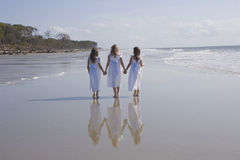 Three Girls Walking the Beach. Three young girls wearing matching white dresses, looking out at the ocean at the beach with full reflections in the sand Stock Photography