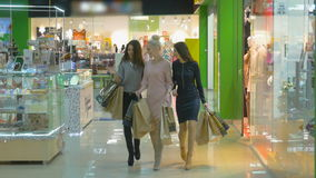 Three Girls are walking near store windows in Shopping Mall. Steadicam shot. stock video