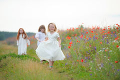 Three girls in white dresses playing outdoors. Selected focus Stock Photo