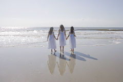 Three Girlss Holding Hands. Three young girls wearing matching white dresses, looking out at the ocean at the beach with full reflections in the sand Royalty Free Stock Photos