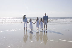 Three Girlss Holding Hands. A family with Three young girls wearing matching white dresses, looking out at the ocean at the beach with full reflections in the Stock Photos