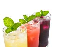 Three glass of apple,grape and strawberry juice Stock Photos