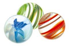 Three glass balls. Three murmur on white base Royalty Free Stock Photo