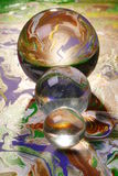 Three glass balls abstract. Three balls of glass in a row on an abstract painting, reflecting it partly, The smallest ball refracts light from behind Royalty Free Stock Photos