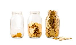 Many gold coins in three glass bottles. Three glass bottles with increasing amounts of gold coins to show how savings grow over time stock photos