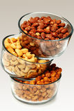 Three glass bowls filled with cashews, salted roasted almonds an Stock Images