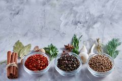 Three glass bowls with spices arranged in rows on white textured background, view from above. Three glass bowls with spices arranged in rows on white textured royalty free stock image