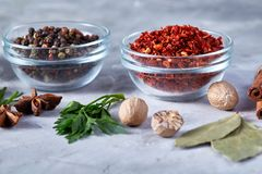 Three glass bowls with spices arranged in rows on white textured background, view from above. Three glass bowls with spices arranged in rows on white textured stock photography