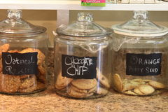 Three glass cookie canisters. With the names of the cookies displayed on a counter in a small town bakery Stock Photo