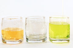 Three glass cups withgreen liquid on a white background. Three glass cups with green liquid on a white background: almost empty and the almost complete, third Royalty Free Stock Photo