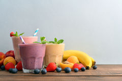 Three glass of fruit milkshakes. Or smoothies with drinking straws and fresh fruits and berries on blue background royalty free stock photo
