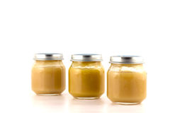 Three glass jars of baby puree fruit stand nearby. On a white background Royalty Free Stock Photo