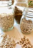 Three glass jars with brown sugar, oatmeal and beer yeast lozenges royalty free stock photography