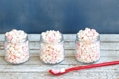 Three glass jars filled to brim marshmallow. Three glass jars filled to the brim marshmallow. with a long red spoon royalty free stock image