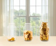 Three glass jars of growing savings on shelf Royalty Free Stock Photo