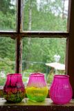 Three glass mugs for candles in front of window Stock Images
