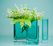 Three glass vases with spring flowers on blue Royalty Free Stock Photos