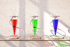 Three glass vessels with liquid. Three glass vessels with colorful liquid on shelf and textured concrete background. 3D Rendering Royalty Free Stock Photography