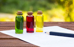 Three glass vials and blank for records on a wooden table. Chemical experiments. School concept. Household experiences Royalty Free Stock Photos