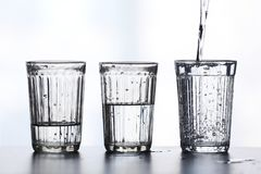 Three glass of water with splashes Stock Photos