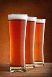 Three glasses of beer. On a wooden table Royalty Free Stock Photography