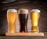 Three glasses of beer on the wooden table. stock photography
