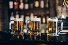 Three glasses with beers in a pub. Background Royalty Free Stock Photography