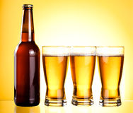 Three glasses and Bottle of fresh light beer Royalty Free Stock Photos