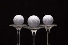 Three glasses of champagne and golf balls Royalty Free Stock Image