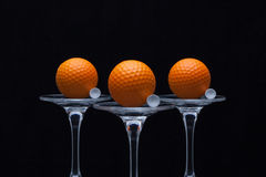 Three glasses of champagne and golf balls Stock Photo