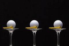 Three glasses of champagne and golf balls Royalty Free Stock Images