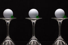 Three glasses of champagne and white golf balls Stock Photos